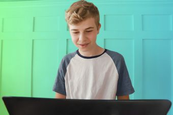 boy sitting at laptop with green gradient on wall behind him