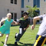 girl and boy running at summer camp